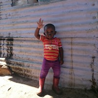 township-child-waves-to volunteers